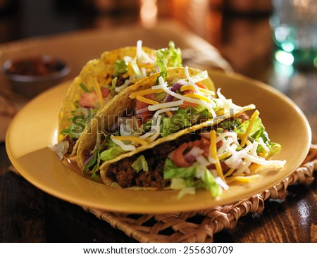 plate of tacos with yellow hard shells and beef - stock photo