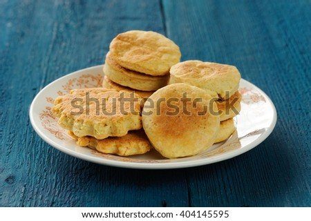 Plate of tasty imperfect homemade cookies on deep blue background - stock photo