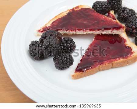 Plate of toast with jam and fresh blackberries - stock photo