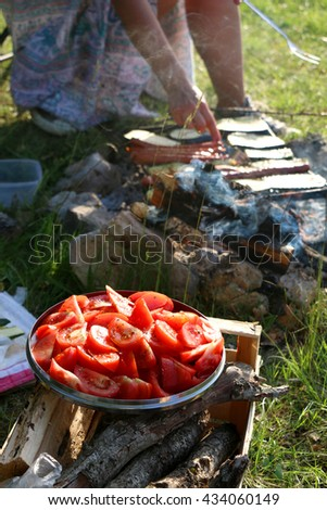 Plate of tomatoes, barbecue in the background, outdoors. Selective focus.  - stock photo