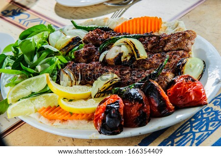 Plate of traditional eastern kebabs. - stock photo