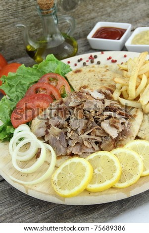 Plate of traditional Greek gyros or Turkish kebab with meat, fried potatoes, tomato and onion - stock photo