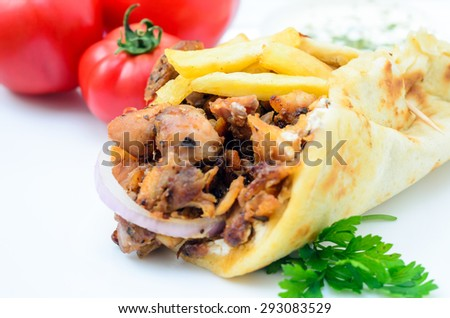 Plate of traditional Greek gyros with meat, fried potatoes, tomato and onion