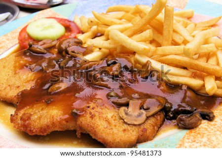 Plate of traditional schnitzel with mushroom sauce and potato fries