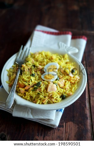 Plate of traditional scottish breakfast dish kedgeree - basmati rice cooked with curry powder, smoked salmon fish, hard boiled eggs, milk - stock photo