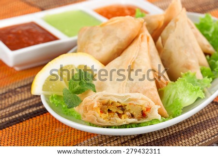 plate of vegetable samosa with indian sauces - stock photo