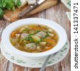 Plate of vegetable soup with meatballs on the wooden table closeup - stock photo