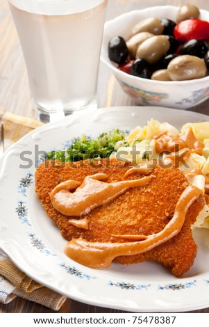 Plate of Wiener Schnitzels with sauce and olives