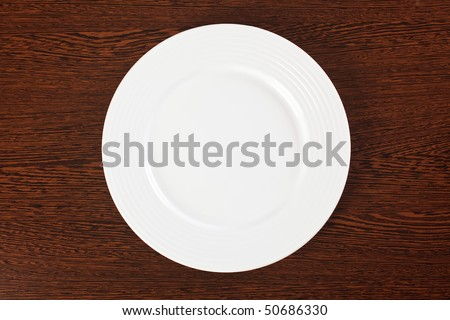 plate on a wooden table - stock photo