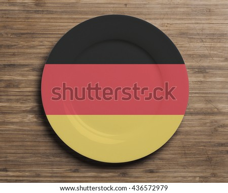 Plate on table with overlay flag of Germany - stock photo