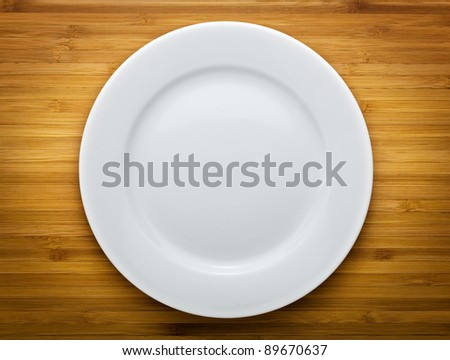 Plate on wood background - stock photo