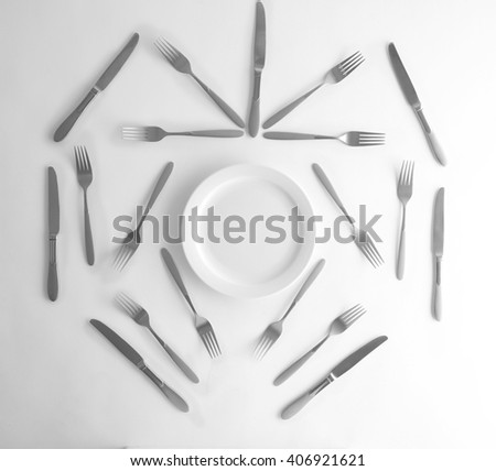 Plate, silver forks and knives, top view - stock photo