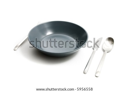 Plate, spoon, knife and fork on white background