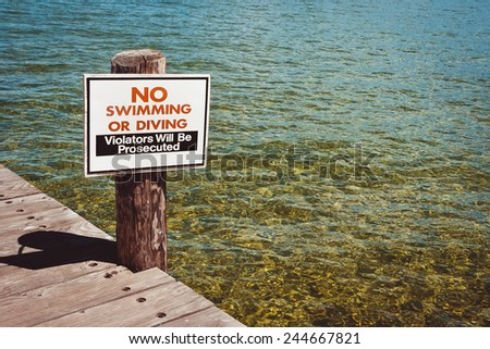 Plate with a ban on swimming in a wooden pier