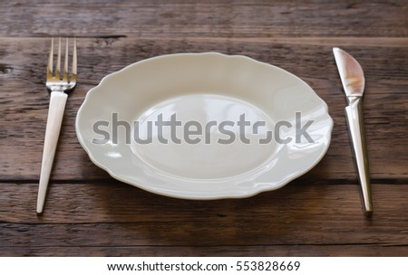 Plate with a fork and knife on a wooden background