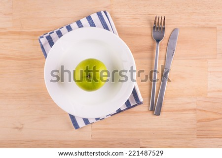 Plate with a green apple as a symbol of diet on white brown wooden table. Above view - stock photo