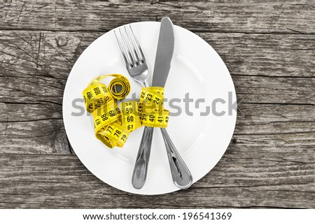 plate with a knife and fork wrapped in measuring tape on a wooden background. diet concept - stock photo
