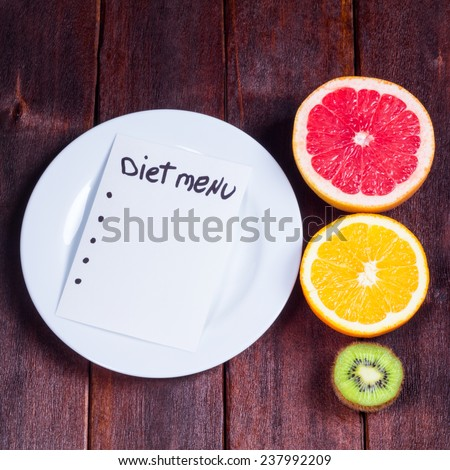 Plate with a note, grapefruit, orange and kiwi on a table. The concept of weight loss and diets. Diet menu. Drafting diet. Fruit on the table. - stock photo