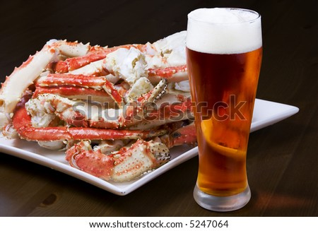 Plate with a pile of crab legs and a glass of amber beer (clipping paths are included) - stock photo