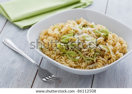 Plate with a vegetarian dish made from sprial pasta and leek.