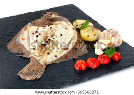 Plate with baked turbot fish with potato slices, seasoned with cherry tomatoes, garlic, parsley, thyme, black and red pepper grains. - stock photo