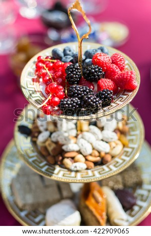 Plate with berries - red current, blackberry, raspberries and and blackberry - in focus and nuts and cakes out of focus on a background - stock photo