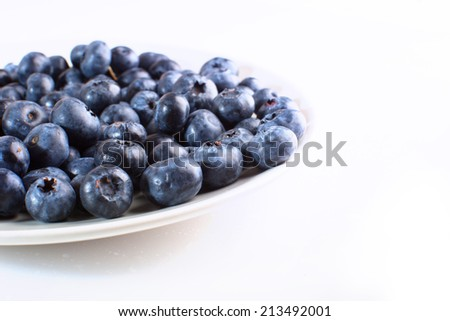 plate with blueberries close-up isolated on white background