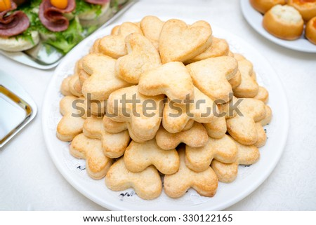 plate with butter cookies with sugar heart shapes. - stock photo