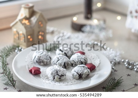 Plate with chocolate cakes on an openwork napkin, surrounded by Christmas decorations - beads, stars, garlands, tree cutting and ceramic house with a candle inside
