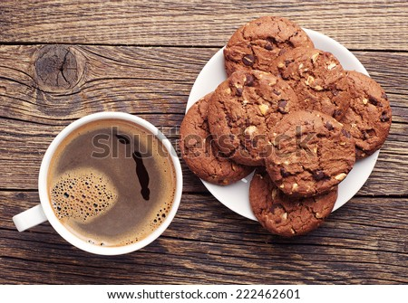 Plate with chocolate cookies and cup of hot coffee on old wooden table. Top view