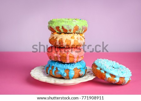 Plate with colorful donuts on pink table