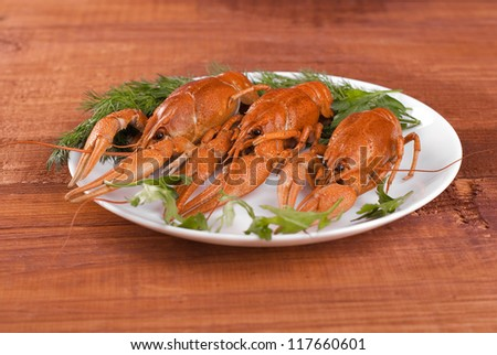 Plate with crayfish on a wooden table. - stock photo