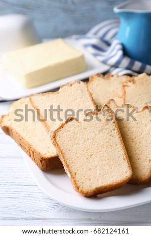 Plate with delicious sliced butter cake on wooden table