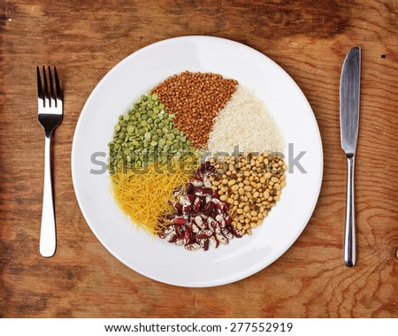 Plate with different cereals and garnish on wooden table. - stock photo