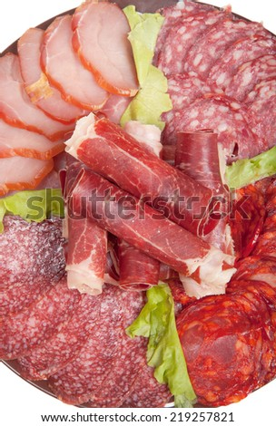 Plate with different meat delicacies isolated on white background. Shallow depth of field