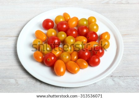 Plate with different tomato cultivars on plank wooden table