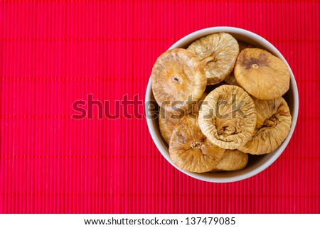 Plate with dried figs, on red tablecloth. - stock photo