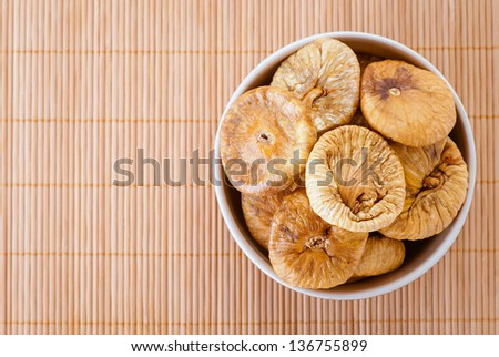 Plate with dried figs, on tablecloth. - stock photo