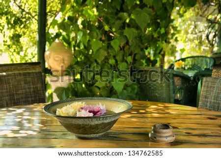 Plate with flowers in outdoor Thai restaurant. Shot in Western Cape, South Africa. - stock photo