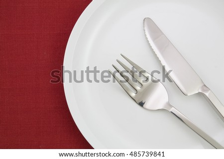 plate with fork and knife on red tablecloth