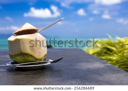 Plate with fresh coconut on the table in the beach cafe - stock photo