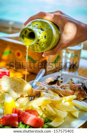 plate with fresh salad, fries, seafood and olive oil - stock photo