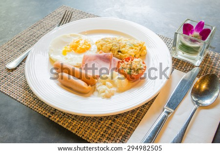 Plate with fried eggs, bacon and chicken sausage on table - stock photo
