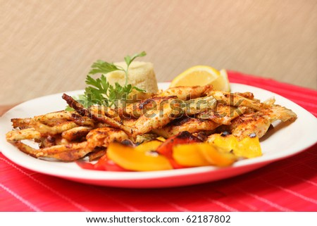 plate with fried frog legs and couscous (shallow DOF) - stock photo
