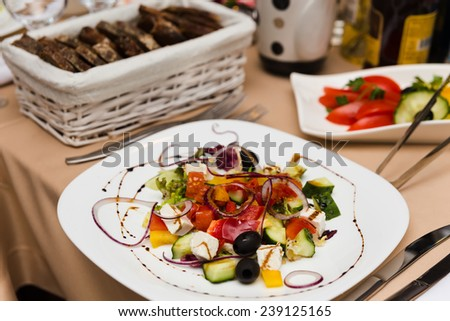Plate with Greek salad on beautifully decorated table in the restaurant - stock photo