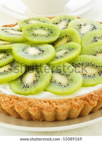 Plate with homemade kiwi tart and coffee cup. Shallow dof. - stock photo