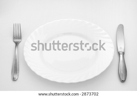 Plate with knife and fork isolated on a white background.