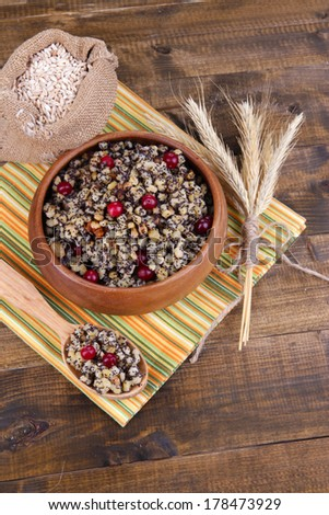 Plate with kutia -  traditional Christmas sweet meal in Ukraine, Belarus and Poland, on wooden background - stock photo