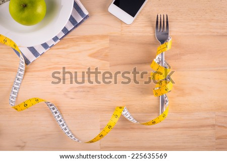 Plate with measure tape, cup, knife and fork. Diet food on wooden table - stock photo