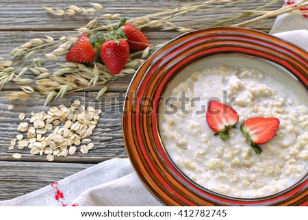 Plate with oat cereal with strawberries and grains on wooden background